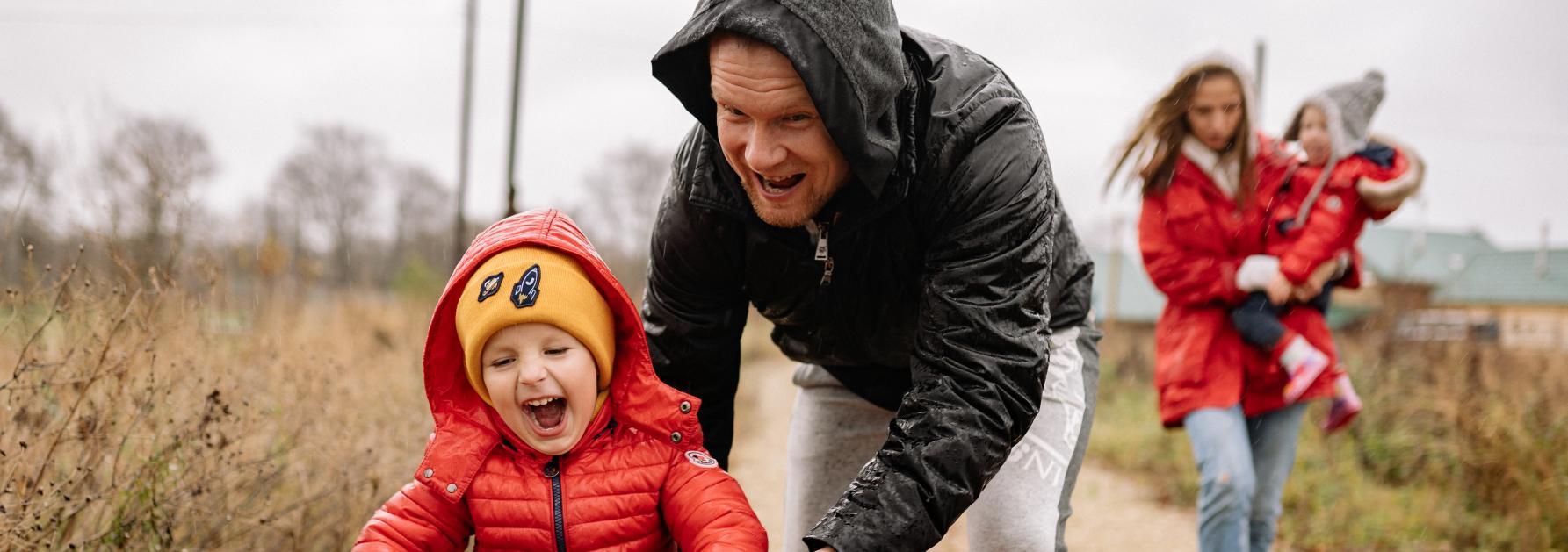 Peuter op fietsje met ouders en regenlaarzen